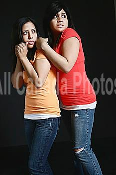 two girls huddling close together looking very afraid