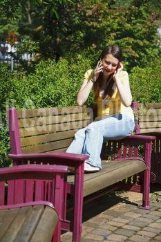 a teenage girl talking on her cellphone on a park bench