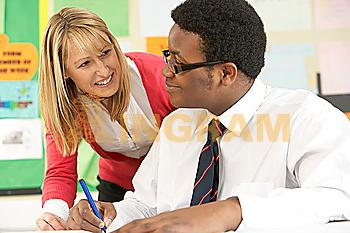 Teenage Student Working In Classroom With Teacher