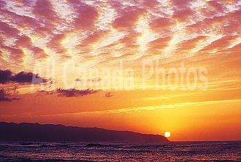 Hawaii, Oahu, North Shore, overview of Waimea Bay at sunset, dramatic clouds.