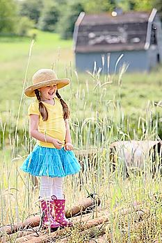 a girl wearing a straw hat and rubber boots on a farm; troutdale, oregon, united states of america