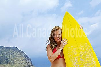 Hawaii, Oahu, Girl on beach with yellow surfboard.